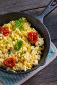 stock photo of scrambled eggs  - scrambled egg with grilled tomato in vintage iron pan from above - JPG