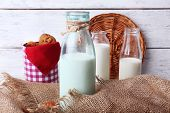 stock photo of caw  - Milk in glassware and walnuts on wooden table with sackcloth - JPG