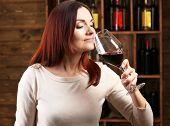 image of wine cellar  - Young woman tasting wine in cellar - JPG