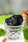 stock photo of prunes  - Prunes and almonds in glasses with leaves on green napkin - JPG