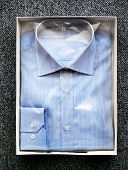 stock photo of button down shirt  - High Angle View of Tailor Made Blue Button Down Dress Shirt Wrapped in Cellophane and Folded in Open Box on Carpeted Surface - JPG