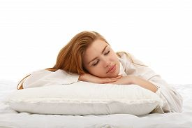 stock photo of freckle face  - Young beautiful girl sleeps in the bed hugging a pillow on his stomach - JPG