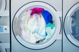 foto of laundromat  - Washing machine full of colorful clothes to be washed - JPG