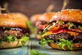 Close-up of home made tasty burgers on wooden table. poster
