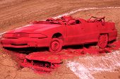 pic of monster-truck  - A red crashed car on top of another red crashed car waiting to get ran over by a monster truck - JPG