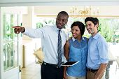 Real estate agent pointing while showing the house to couple poster