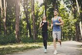 Young Happy Sporty Couple Jogging In Green Park During Morning Workout, Copy Space poster