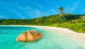 Beautifully shaped granite boulder in the turquoise sea  and a perfect white sand at Anse Coco, La D poster