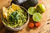 Tortilla Chips In A Bowl Of Guacamole Dip With Avocado Limes And Cherry Tomato Ingredients poster