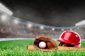 Baseball Helmet, Bat, Glove And Ball On Grass In Brightly Lit Outdoor Stadium With Focus On Foregrou poster