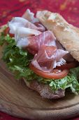 Italian submarine sandwich with cured meat, lettuce and tomato poster
