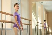 Happy Young Ballerina At Class. Beautiful Young Smiling Ballet-dancer Standing Near Barre At Ballet  poster