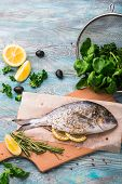 Cooking Raw Dorado Fish With Spinach, Rosemary, Olives, Herbs, Spices And Lemon Closeup On Wooden Cu poster