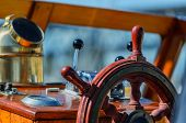 Red, Old, Lacquered, Wooden Steering Wheel On A Marine Yacht Close-up, Compass In The Background poster