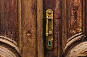 Vintage Background. Brass-made Old Handle With Elements Of An Carved Wooden Door Decorated With Mass poster