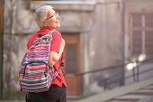 Senior Old Woman Tourist With A Backpack Preparing To Leave Her Home To Go Travelling poster