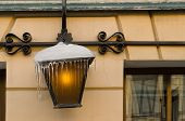 A Few Icicles Hang From A Street Lamp. The Lamp In The Lamp Is On. In The Background, The Wall Of Th poster