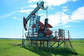 foto of nonrenewable  - Oil Pump Jack In a field pumps petroleum - JPG