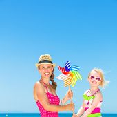 Mother And Daughter On Beach Holding Colorful Windmill Toy poster
