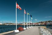 Flags Of Scandinavian Countries Waving On Flagpoles On The Shore. Scandinavian Coastal City. poster