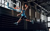 Black Professional Black Basketball Player In Action In A Basketball Court. poster