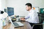 Confident Young Male Stock Broker Trading Through Computer At Desk poster