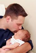 picture of newborn baby  - a father holding and kissing his newborn son showing love - JPG