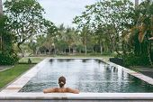 Young girl swimming in infinity pool with in private villa resort. Travelling to Ubud, Bali. poster