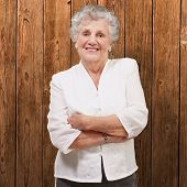 picture of beautiful senior woman  - portrait of an adorable senior woman standing against a wooden wall - JPG
