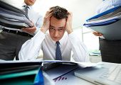 Perplexed accountant touching his head being surrounded by business partners with huge piles of docu