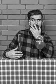 Man In Checkered Shirt Near Bottle, Brick Wall And Blue Tablecloth Background. Barman With Beard On  poster