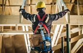 Wood House Construction Challange. Caucasian Carpenter Contractor Wearing Safety Harness In Front Of poster