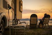 Scenic Rv Campsite Pitch. Camper Van In The Recreational Vehicles Park. Woman Relaxing On A Chair An poster