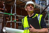 Thoughtful middle aged man, male builder foreman, worker, contractor or architect on construction si poster