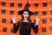 Image of pretty witch girl in black halloween costume pointing fingers upward at copyspace isolated  poster
