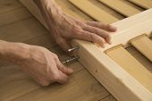 Furniture, Home And Moving Concept - Close Up Of Male Hands Assemblying Home Furniture. poster