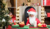 Santa Claus. Christmas Food And Drink. Kid Santa Claus Enjoying In Served Gingerbread Cake And Milk. poster