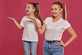 Mom And Daughter With A Funny Ponytails, Dressed In White T-shirts And Blue Denim Jeans Are Posing A poster