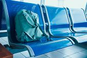 Lounge With Seats In The Airport, Blue Tone. Green Travel Backpack On Seat At Airport Terminal. Dela poster