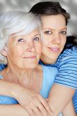 picture of old couple  - Grandmother embraced from her granddaughter both in cyan shirts smiling happy - JPG