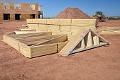 picture of rafters  - Roof rafters stacked up on a construction site for a large building and waiting for instaliation - JPG