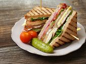 foto of pickled vegetables  - Photo of a club sandwich made with turkey bacon ham tomato cheese lettuce and garnished with a pickle and two cherry tomatoes.