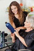 Young female hairdresser advising hair color to senior customer at parlor