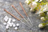 stock photo of placebo  - alternative medicine with homeopathic herbal pills and acupuncture needles - JPG