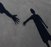 image of student  - Helping Hand with a shadow on pavement of an adult hand offering help or therapy to a child in need as an education concept of charity towards needy kids and teacher guidance to students who need tutoring - JPG