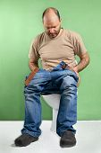 foto of diarrhea  - Man sitting on toilet with diarrhea caused by stomach flu - JPG
