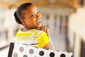 cheerful african young lady in shopping mall