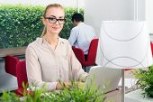 Portrait of beautiful environmentalist with laptop at desk sitting in a hot desk office