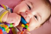 pic of teething baby  - Smiling and playing baby with teething ring - JPG