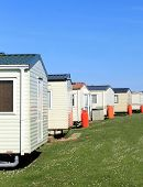 pic of trailer park  - Scenic view of row of caravans in trailer park with blue sky background - JPG